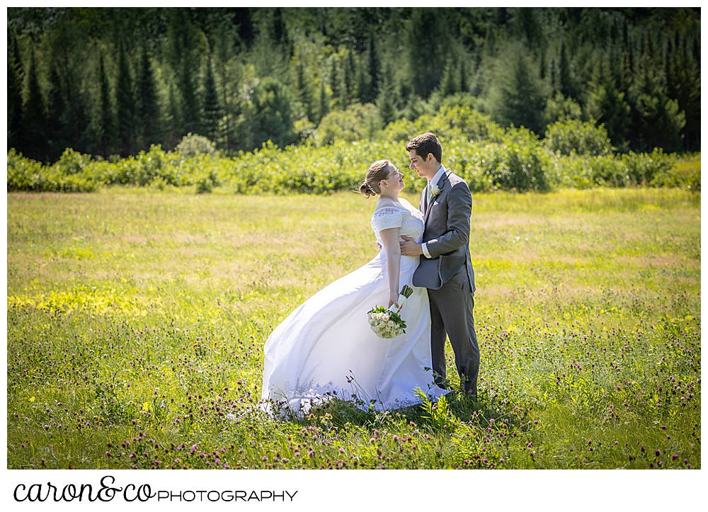 a bride and groom stand in a field, facing each other, their arms around each other