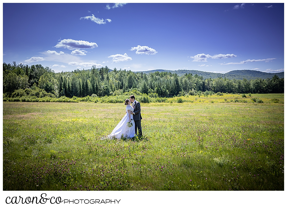 a bride and groom stand in a field, kissing, the mountains in the background, of a sweet western Maine wedding