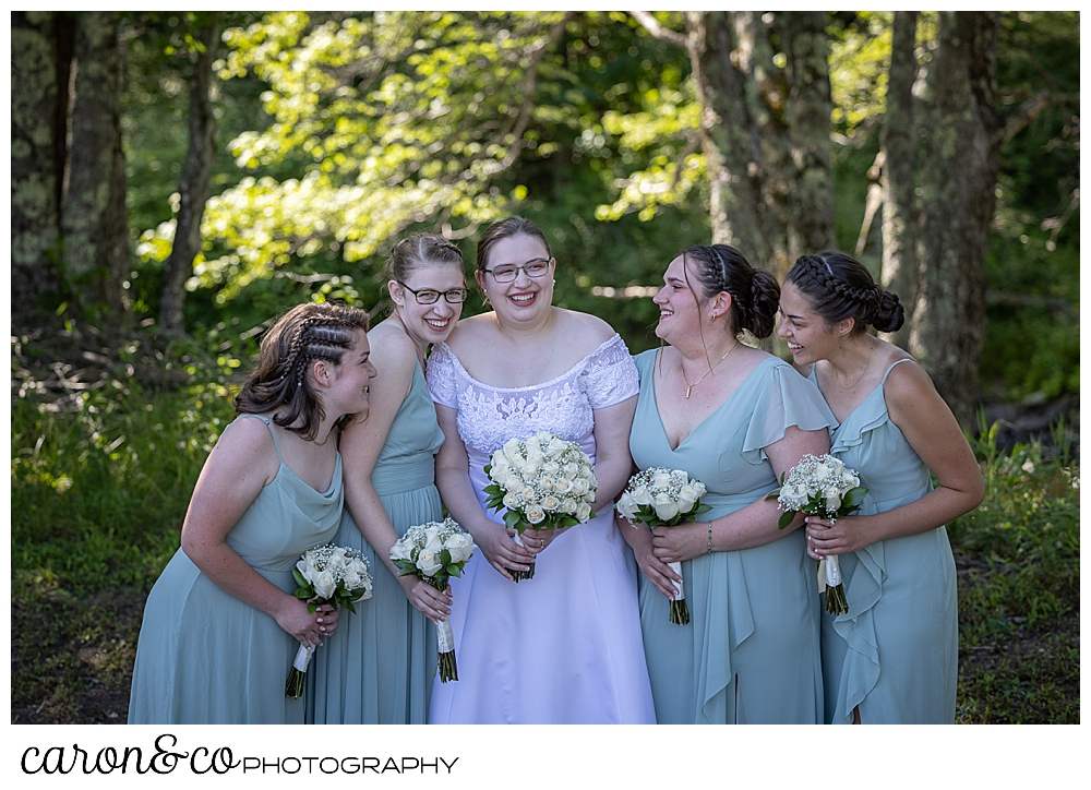 a bride in white, and her bridesmaids in sage green, huddled together, laughing