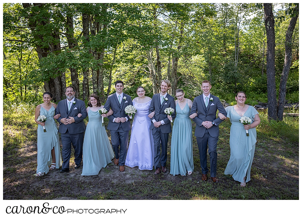 a bridal party with linked arms, walks towards the camera