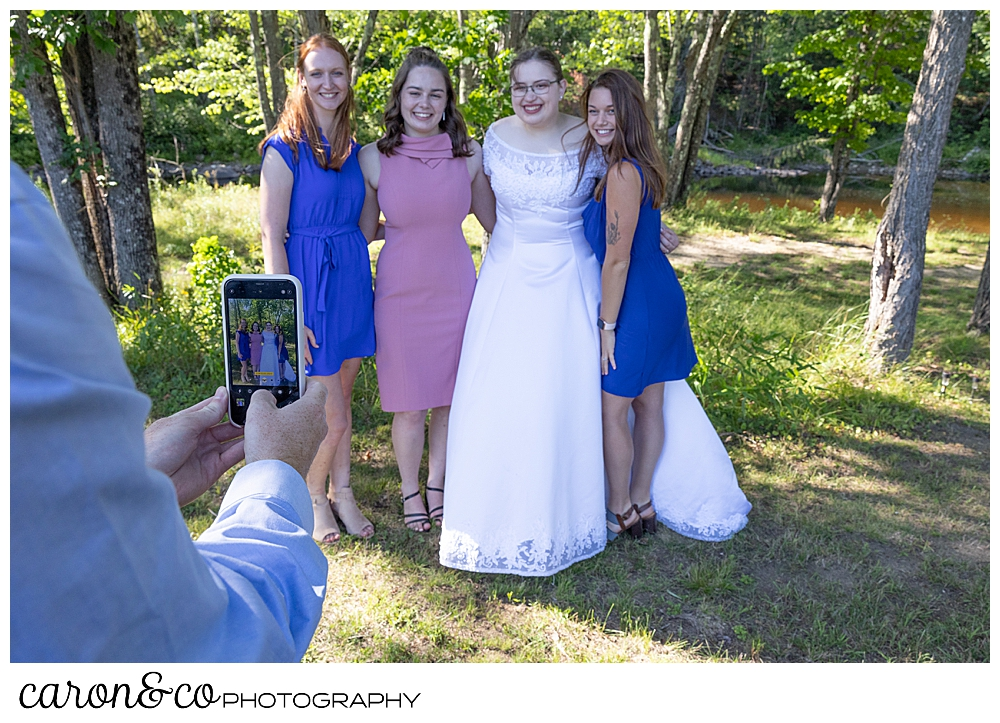 a bride and her friends standing together, while they get their photo taken with a friends phone