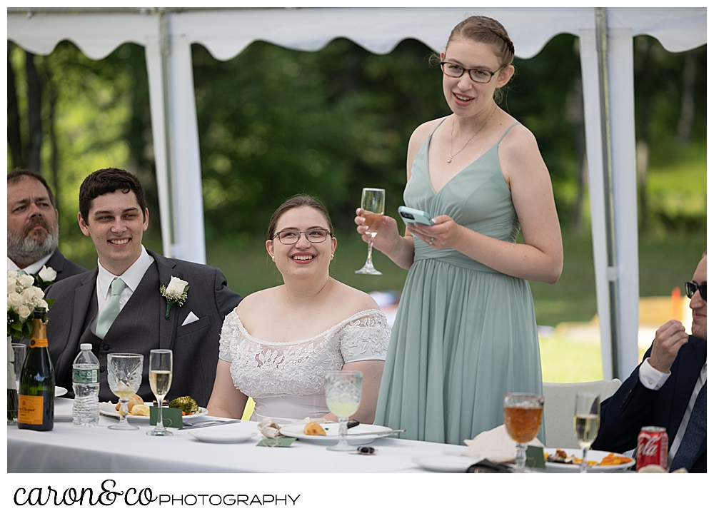 a bridesmaid holds a glass of champagne and her phone during a toast at a sweet western Maine wedding reception
