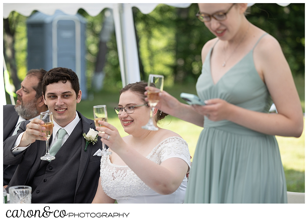 a bride and groom raise their champagne glasses for a toast while a bridesmaid reads her phone