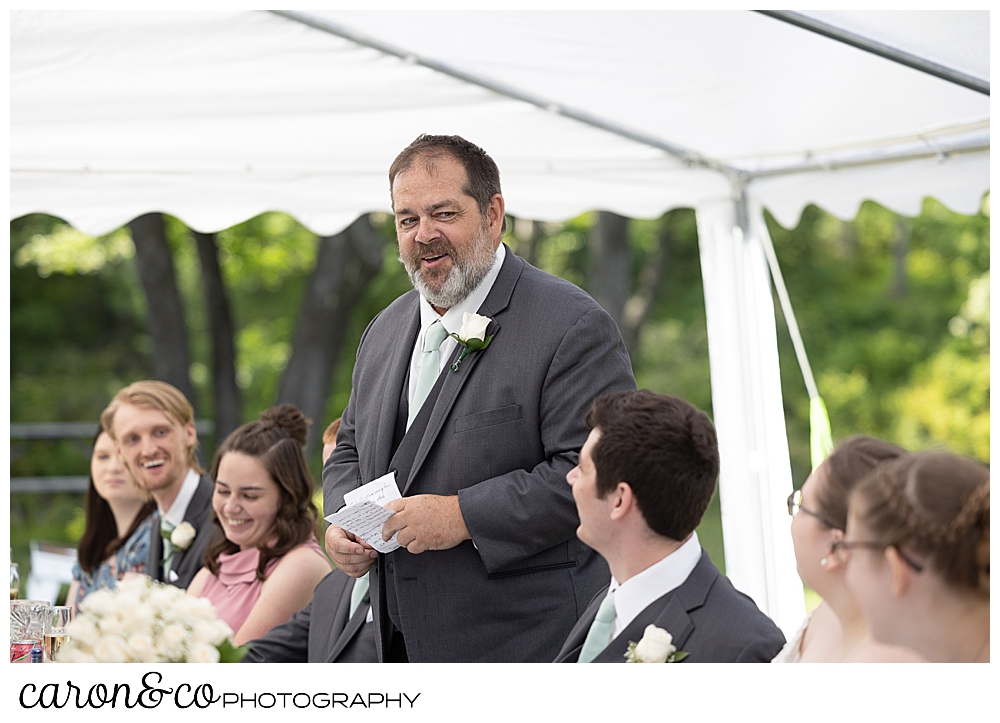 the father of the groom stands to make a toast during a sweet western Maine wedding reception