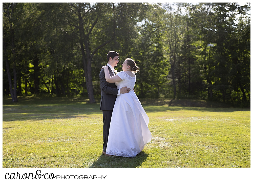 a bride and groom dance in a field during their sweet western Maine wedding reception