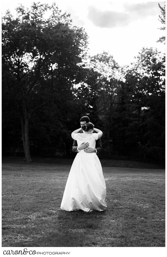 black and white photo of a bride and groom dancing in a field, the bride's back is to the camera