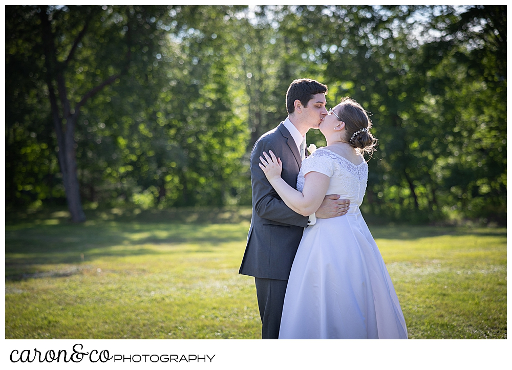 a bride and groom kiss during their first dance in a field during their sweet western Maine wedding reception
