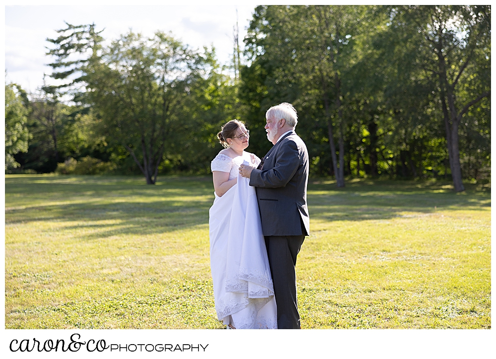 a bride and her father dance in a field during a sweet western Maine wedding reception