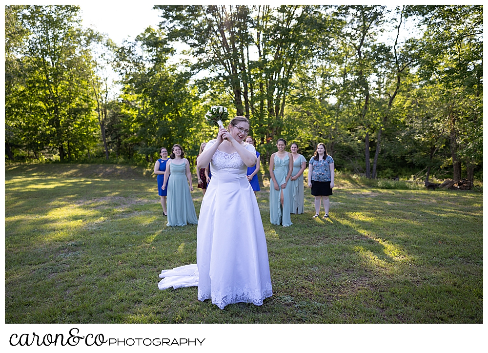 a bride stands ready to toss her bouquet, while the single ladies gather behind her