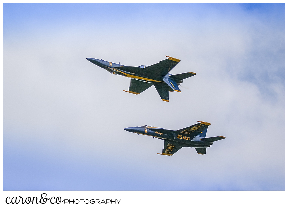 2 navy blue angels flying side by side one of them is flying upside down