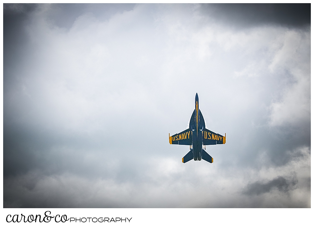 a us navy blue angels airplane, nose up to the sky among the clouds over Brunswick, Maine