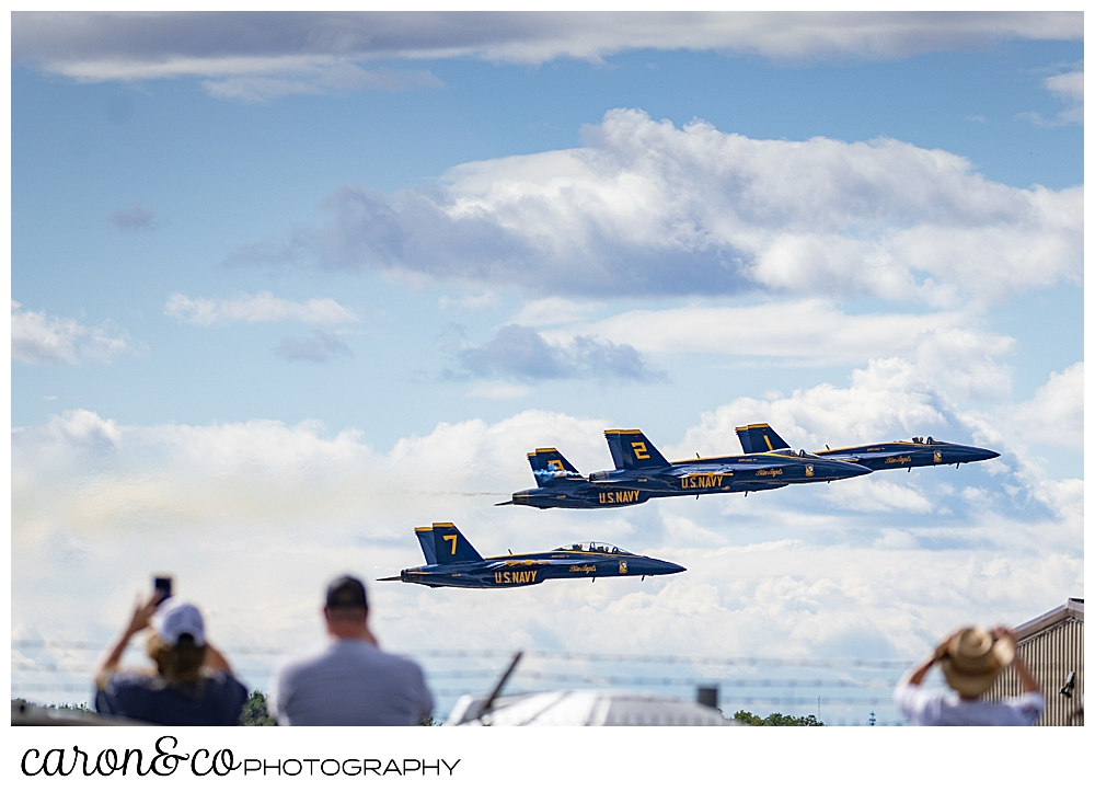 4 us blue angels airplanes flying low in the background, as spectators watch and take photos in the foreground