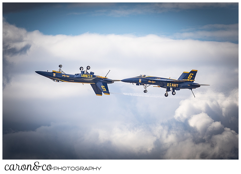 2 us navy blue angels flying in a line, the front plane is upside down