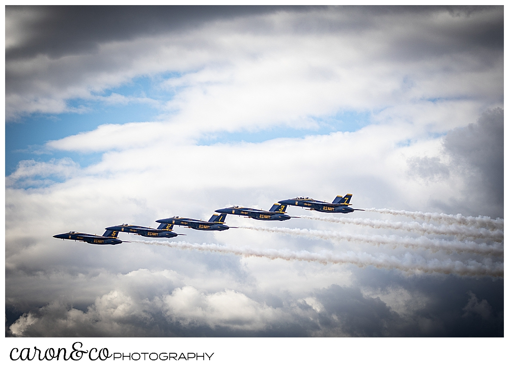 5 us navy blue angels fly together in a wavy pattern
