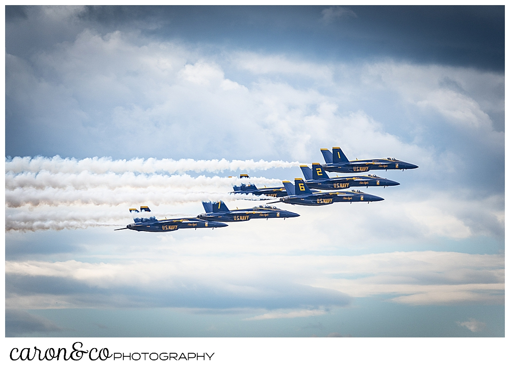 5 us navy blue angels flying side by side among the clouds over Brunswick maine