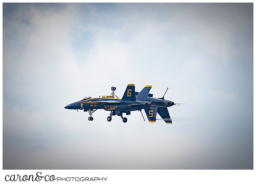 two us navy blue angels flying side by side, one of them upside down