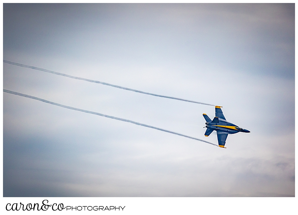 a us blue angel flies with two streams of exhaust
