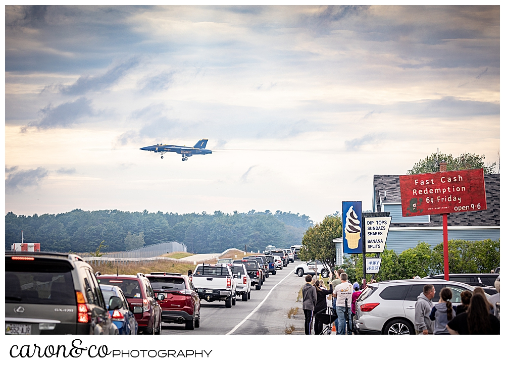 a us navy blue angel flies over Brunswick, Maine, as lines of cars stop to watch