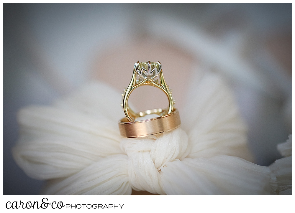 wedding bands and engagement ring atop a bride's shoe