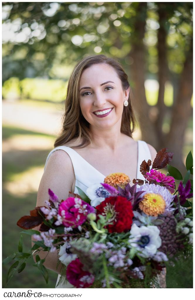 beautiful bridal portrait of a smiling bride, holding a bouquet of brightly colored flowers
