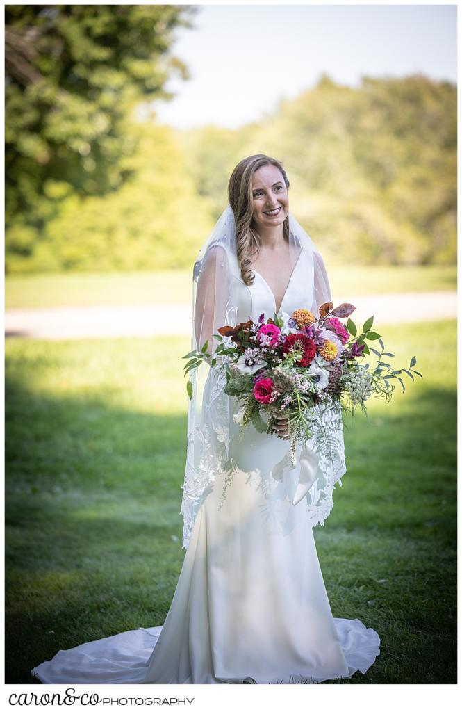 a bride in a white sleeveless wedding dress and veil, carrying a brightly colored bouquet, smiles during her Camp Skylemar wedding day first look