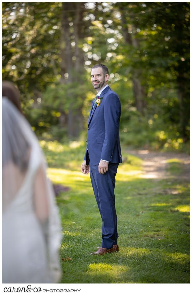 a groom, in the background, wearing a blue suit, turns to see his bride in the foreground, during their camp skylemar wedding day first look