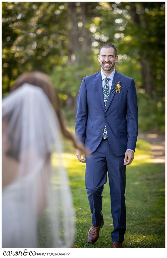 a groom wearing a blue suite, smiles and walks toward his bride in the foreground