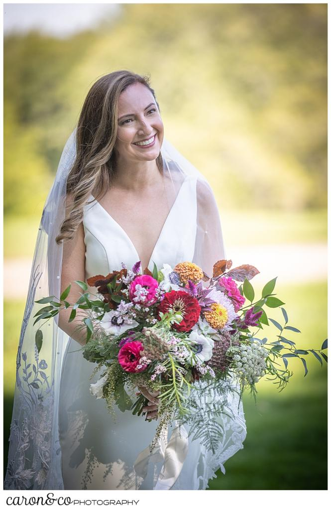 a bride wearing a sleeveless white dress and veil, carrying a bride bouquet of flowers, smiles as her groom approaches during their Camp Skylemar wedding day first look