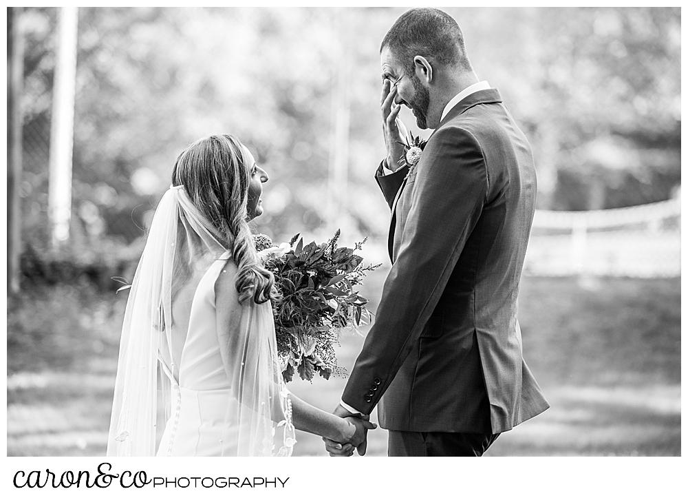 a black and white photo of a bride and groom facing each other, holding hands, the groom as his hand to his eyes, during their Camp Skylemar wedding day first look