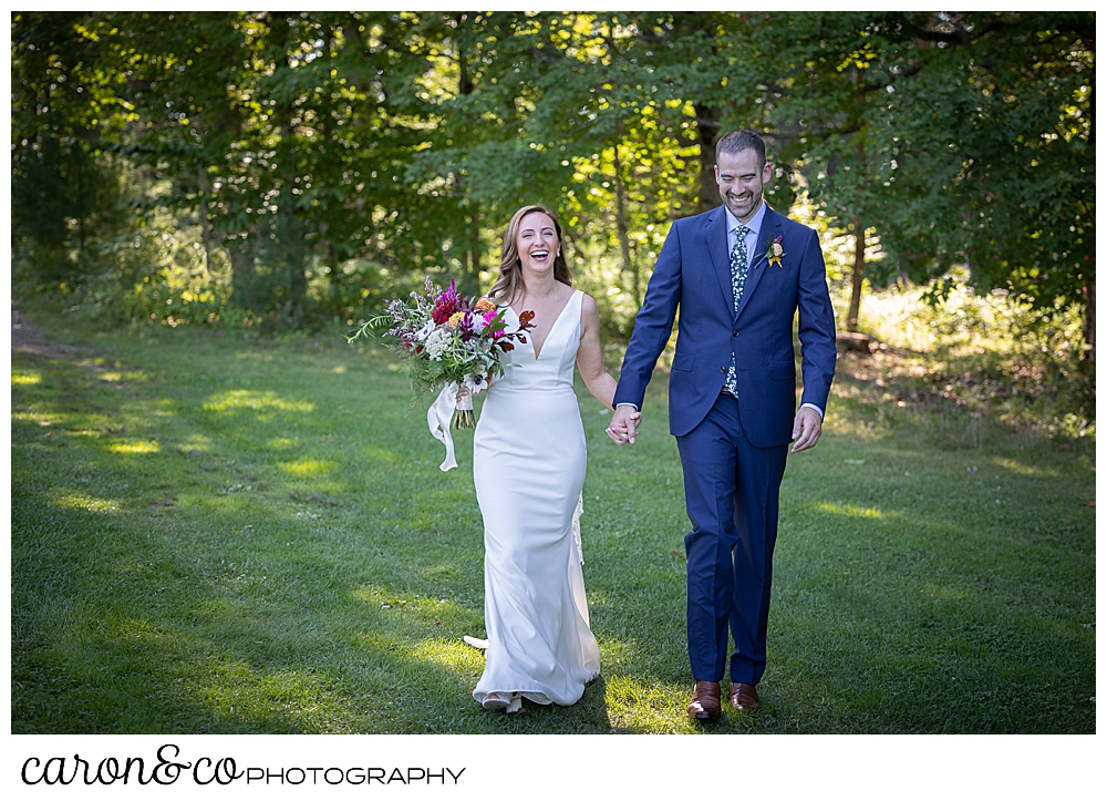 a smiling bride and groom walk hand in hand in a grassy field