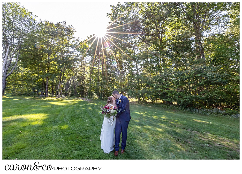 a bride and groom kissing in a grassy field, surrounded by trees