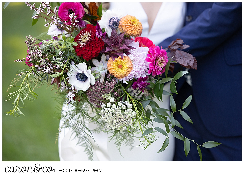a bridal bouquet of bright flowers by Bounty O Blooms, is held by the bride as the groom hugs her