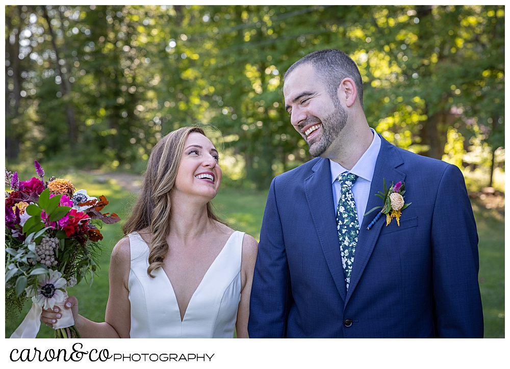 a bride and groom look at one another and smile, the bride is holding her bouquet of fall flowers