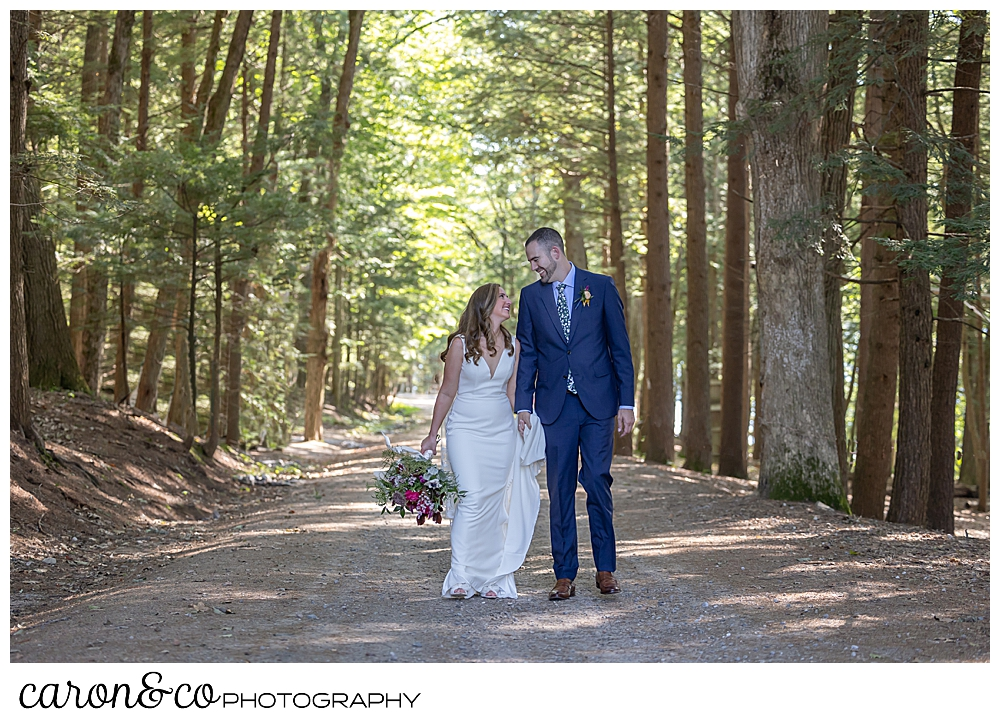 a bride and groom walk hand in hand down a dirt road lined with tall trees