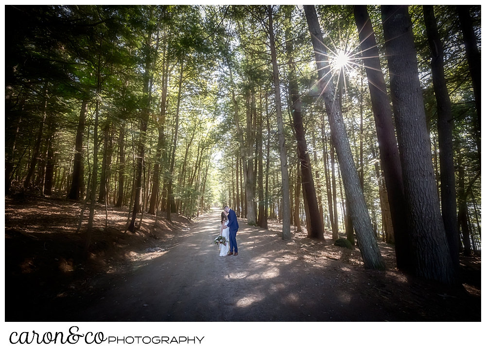 a bride and groom kiss while walking on a dirt road with tall trees all around