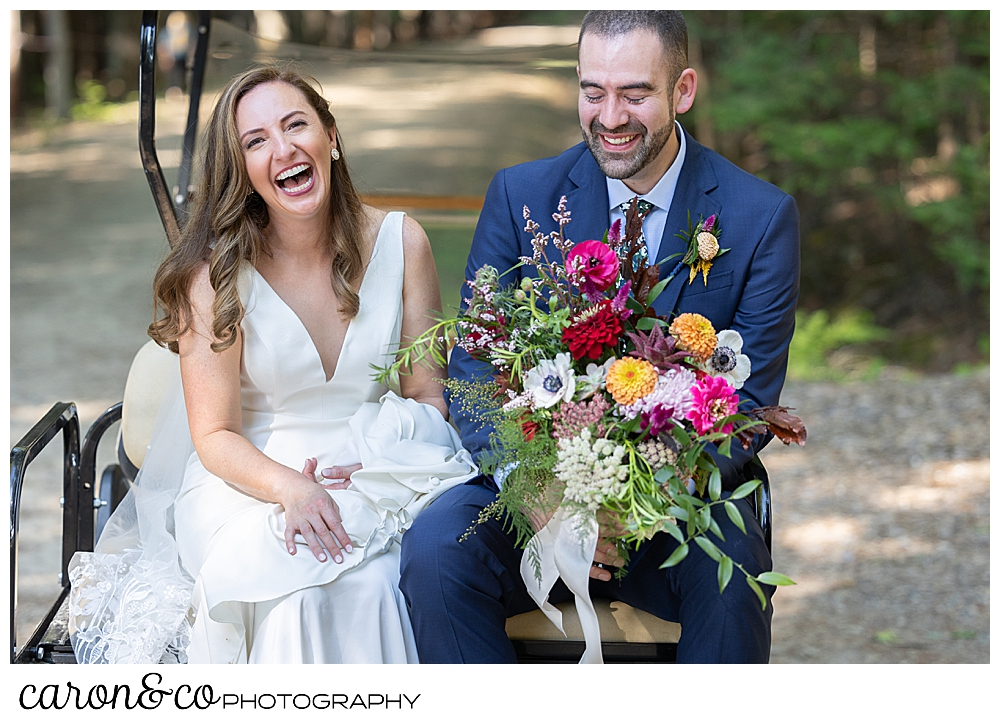 a bride and groom sit together on the back of a golf cart, the bride is laughing and the groom is smiling as he holds the bride's bouquet