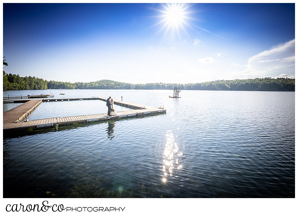 a bride and groom stand together on the dock at Camp Skylemar, Naples, Maine