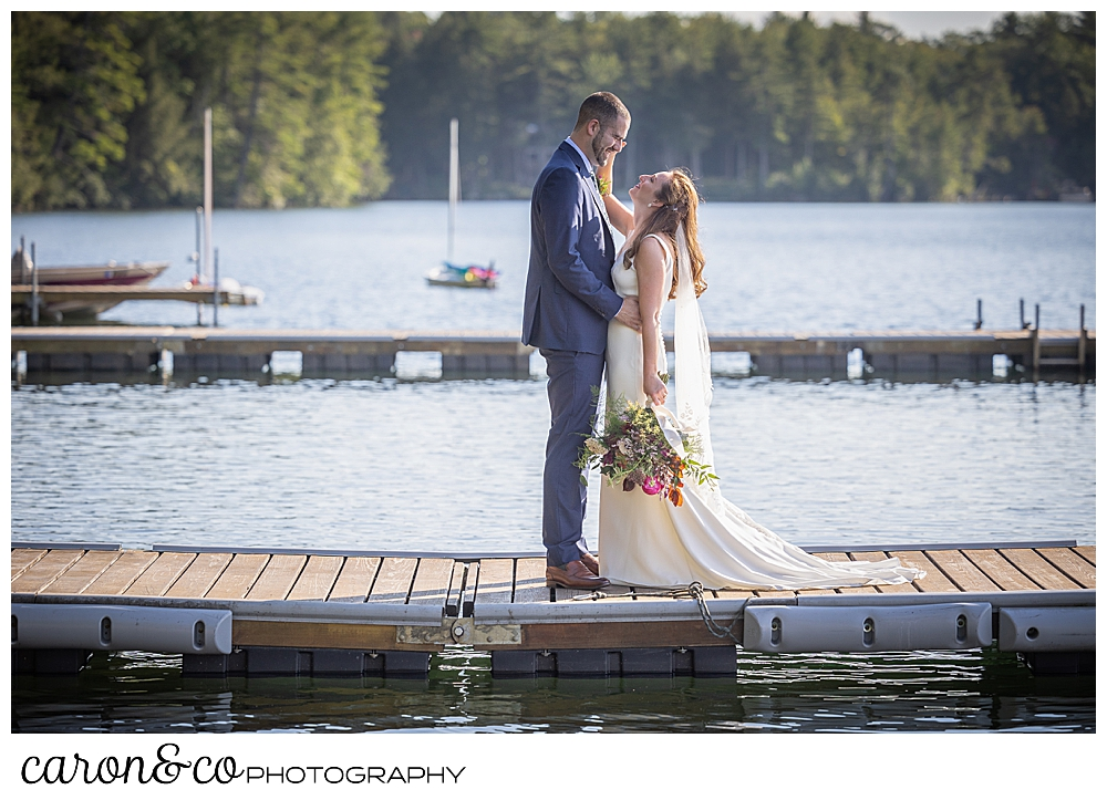a bride and groom standing face to face on the dock at Camp Skylemar, Trickey Pond, Naples, Maine