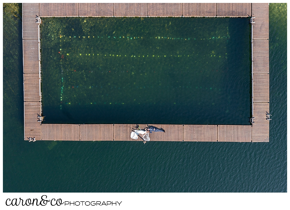 a drone photo of a bride in a white dress, and a groom in a blue suit, lie on a dock at Camp Skylemar on Trickey Pond in Naples, Maine