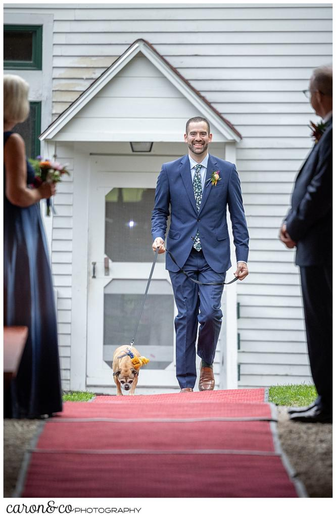 a groom wearing a blue suit, with a small dog on a leash, walks down a red carpet toward the ceremony site under the pavilion at Camp Skylemar