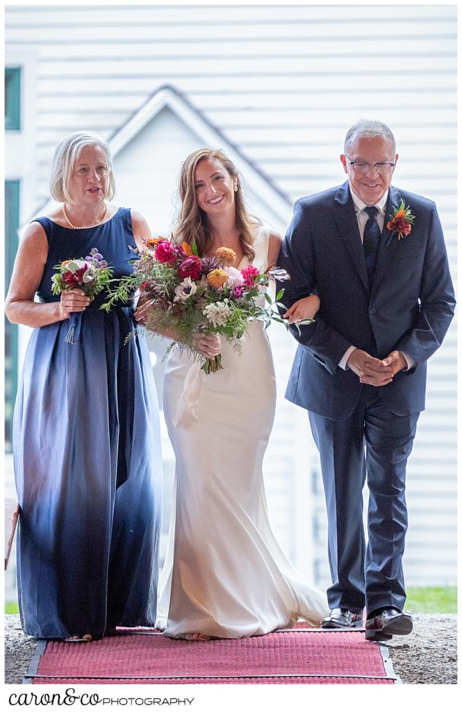 a bride walks down the aisle with her mother and father on either side