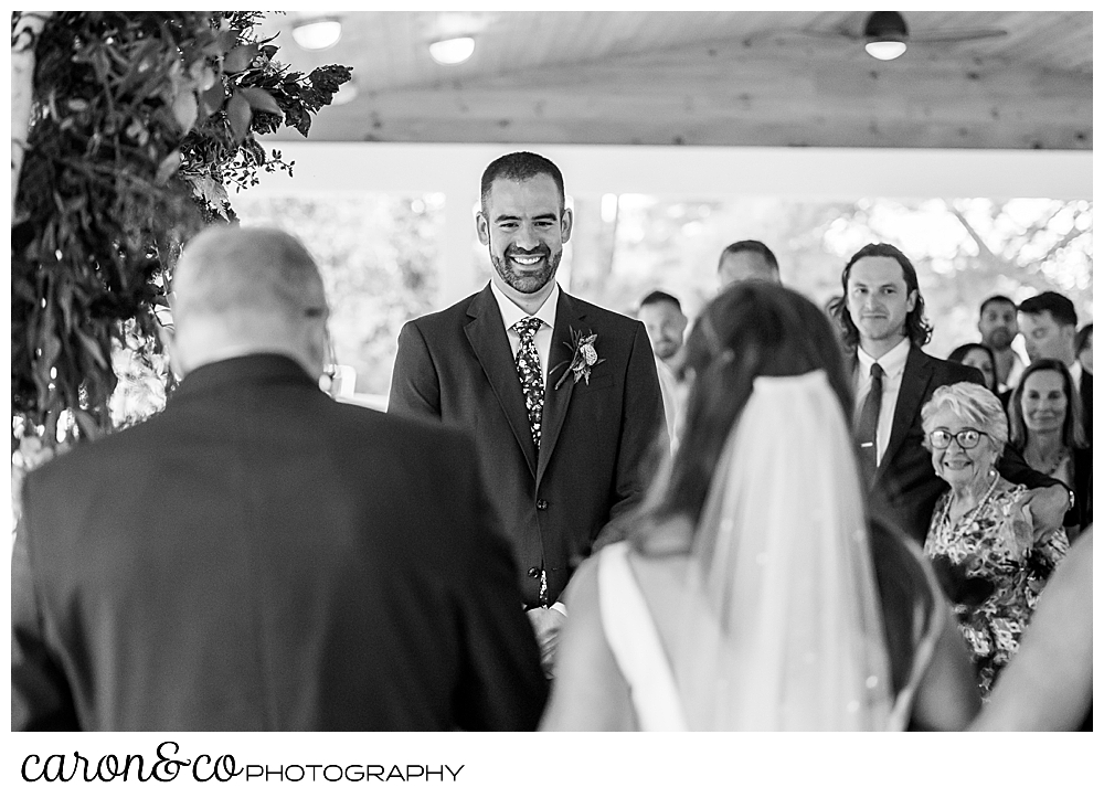a black and white photo of a smiling groom in the background, and the backs of the bride and her father