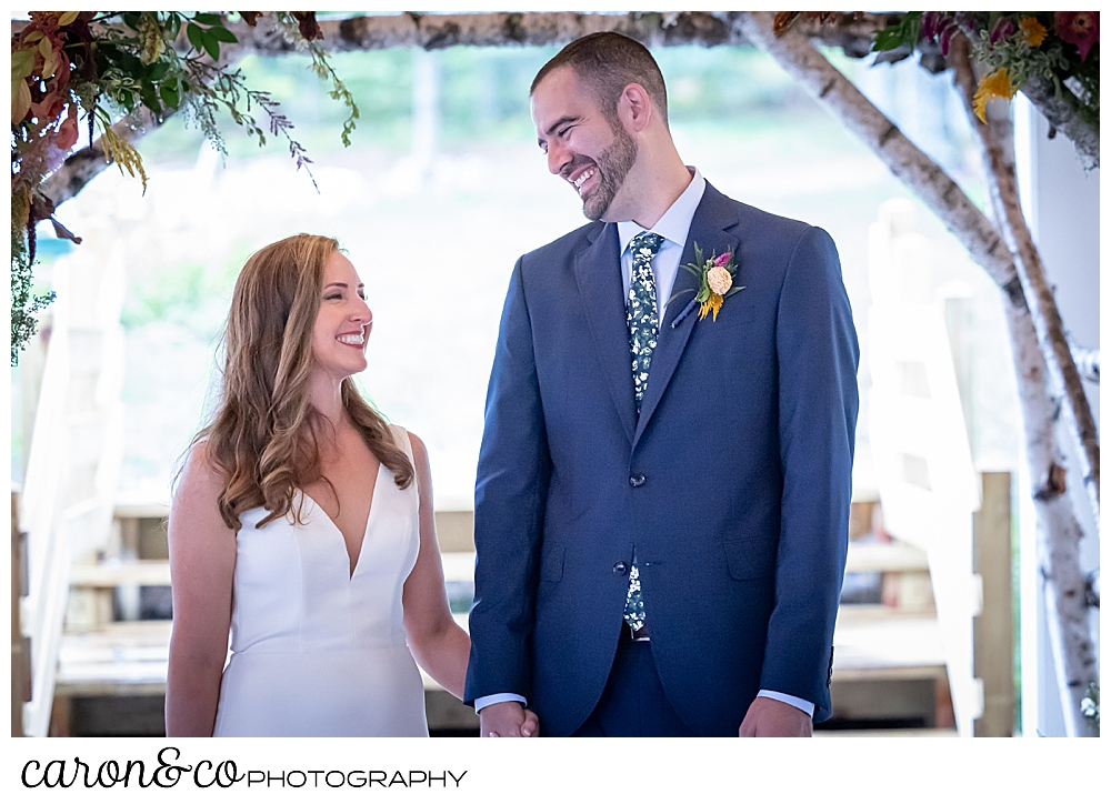 a smiling bride and groom stand under an arbor at their Camp Skylemar wedding ceremony