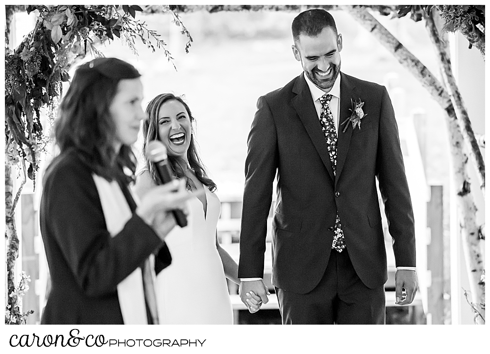 a black and white photo of an officiant holding a microphone in the foreground, and a laughing bride and groom holding hands in the background