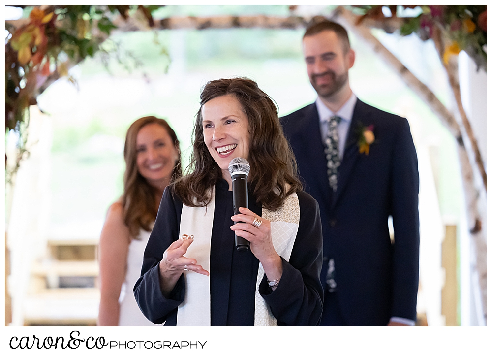 a reverend who is smiling and holding a microphone is in the foreground, a smiling bride and groom are behind her