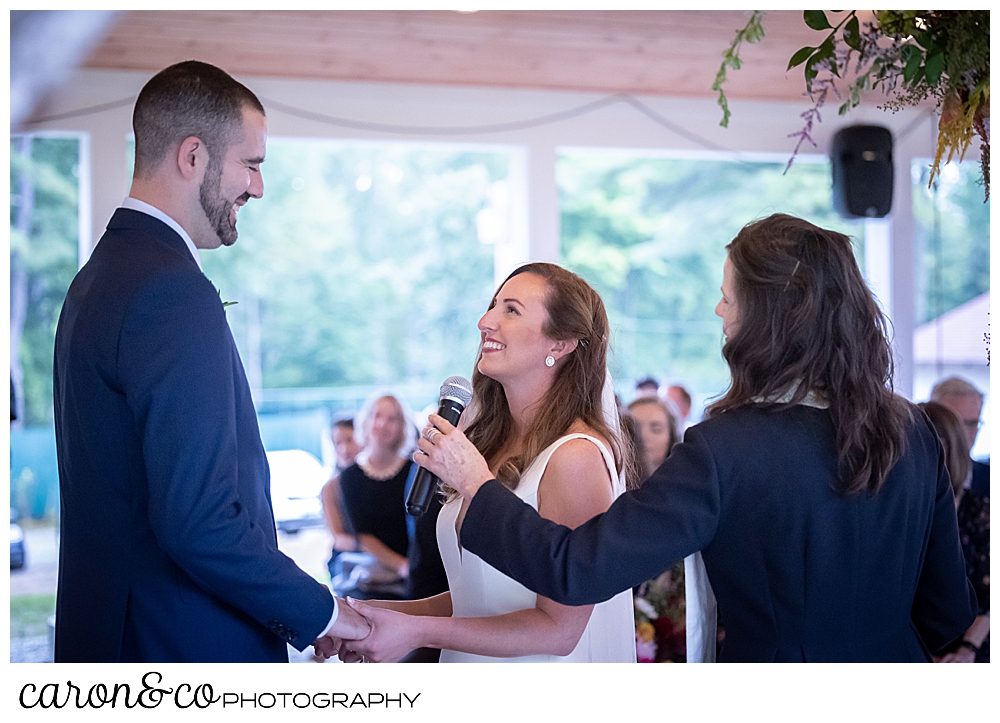 a bride and groom are standing facing one another, holding hands, the bride is smiling at the groom, as the Reverend holds a microphone for the bride to speak her vows