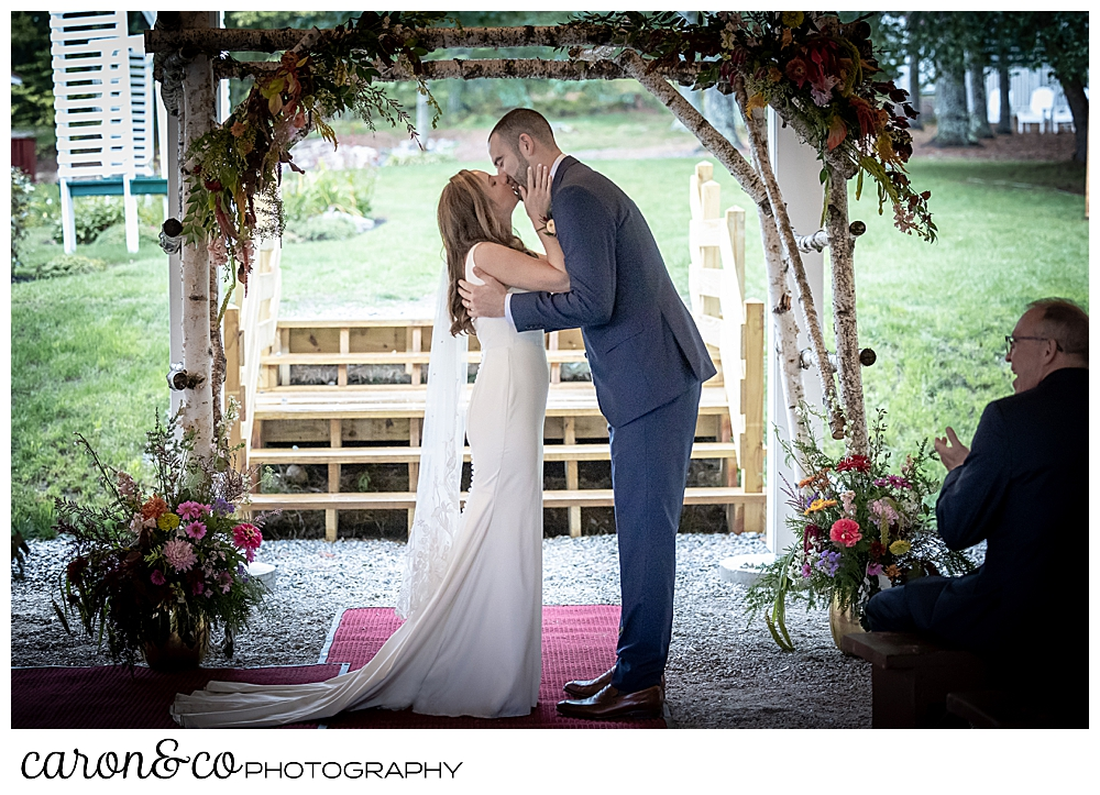 a bride and groom have their first kiss under a birch branch arbor at a camp skylemar wedding ceremony