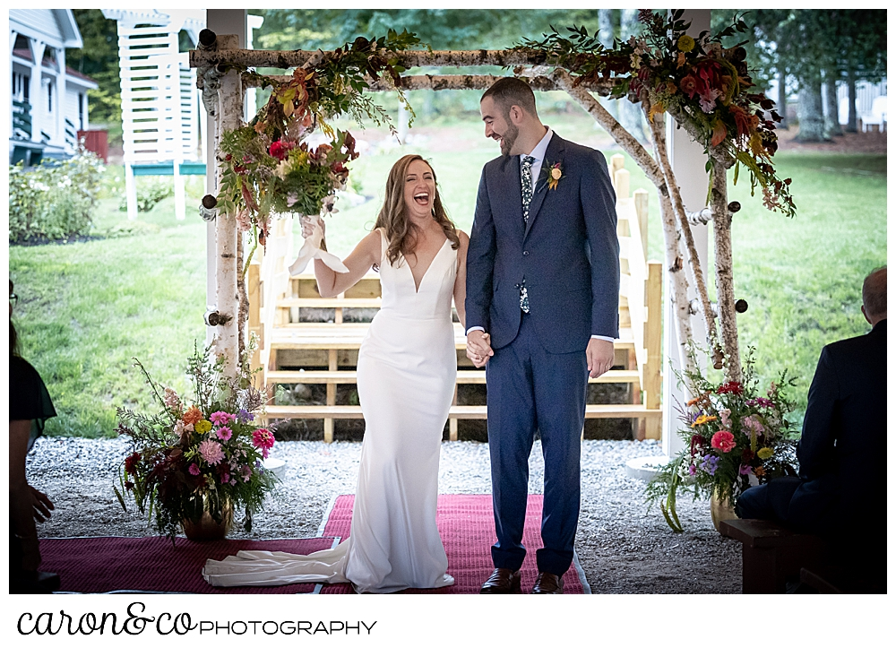 a smiling bride holds the hand of her smiling groom, and her bouquet is held aloft