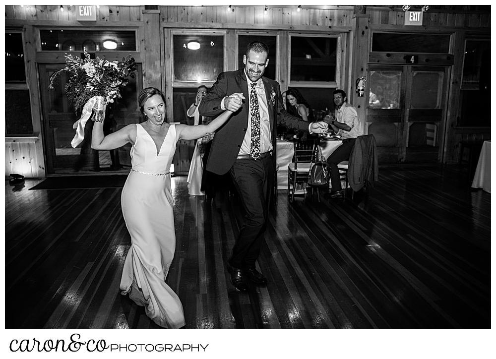 black and white photo of a bride and groom entering their camp skylemar wedding reception, they're both laughing