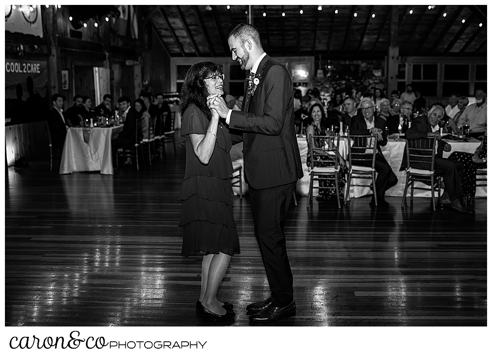 black and white photo of a groom dancing with his mother during the mother son dance